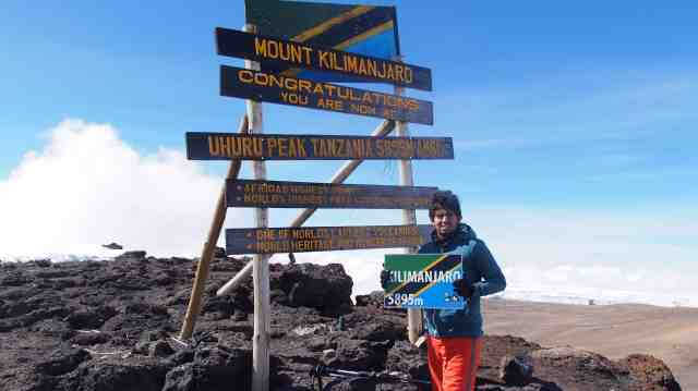 Standing on the peck of Mount Kilimanjaro holding the Tanzanian flag