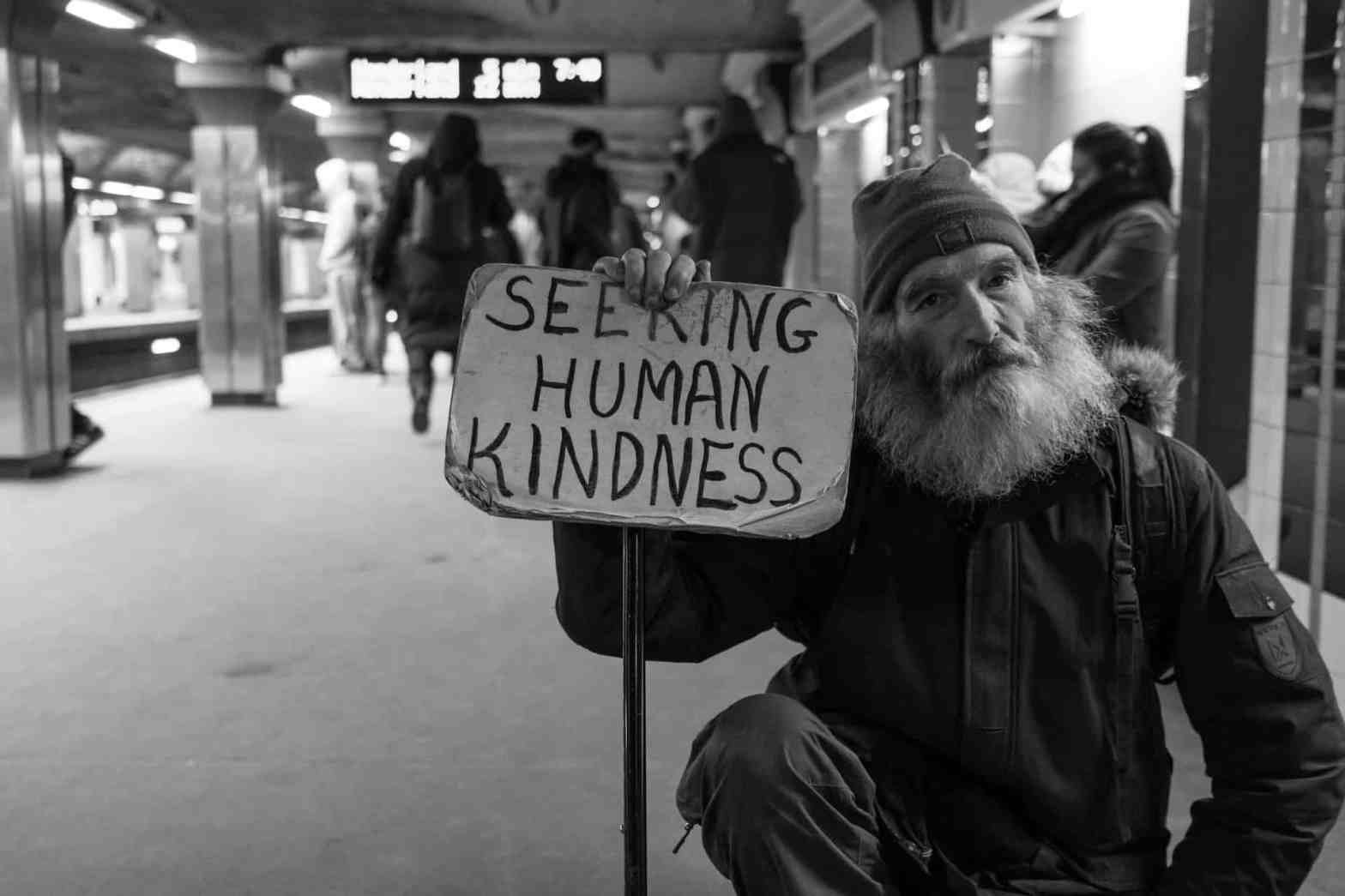 Black and white photograph of an old man holding a sign in adversity