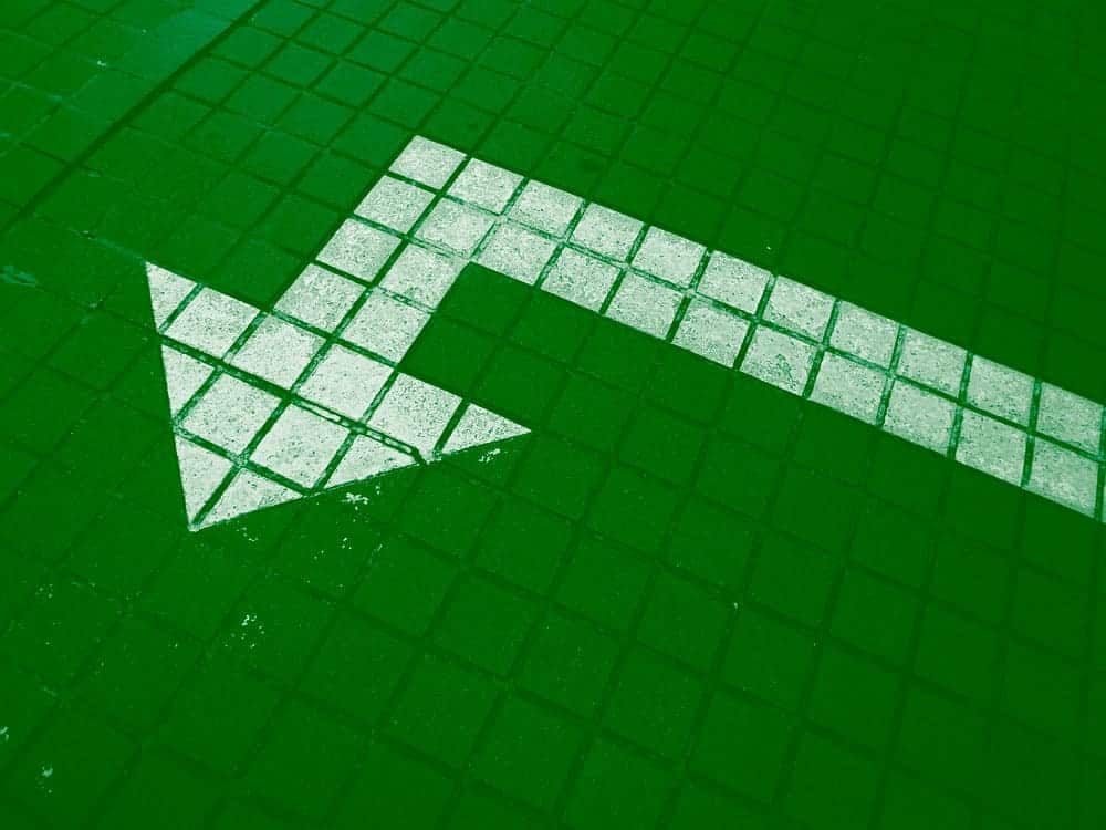 green image of white arrow pointing to the side, getting direction when trying to find purpose.